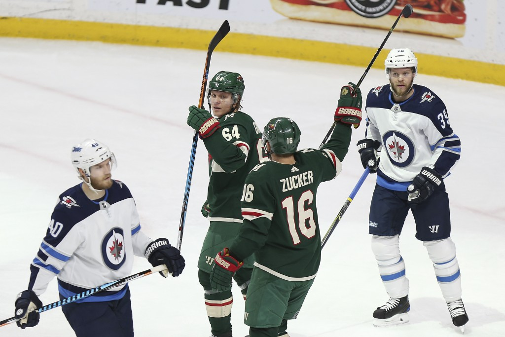 Minnesota Wild's Mikael Granlund (64) looks back at teammate Jason Zucker (16) after Granlund scored a goal against the Winnipeg Jets in the first per