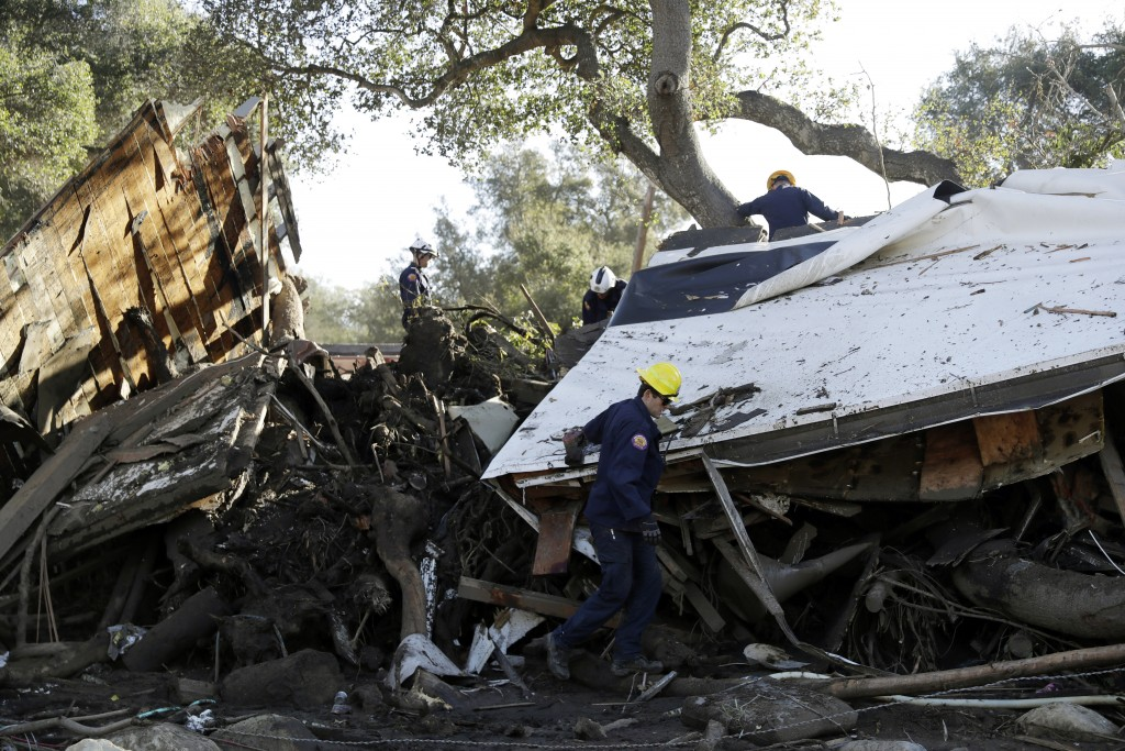 Search and rescue personnel scan a home in the aftermath of a mudslide Saturday, Jan. 13, 2018, in Montecito, Calif.  Most of the people of Montecito,