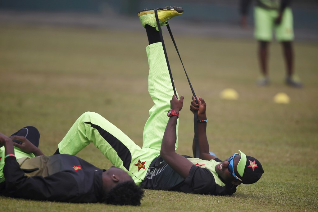 Zimbabwe cricketer Chris Mpofu, right, and his teammate stretch during a training session ahead of the Tri-Nation one-day international cricket series