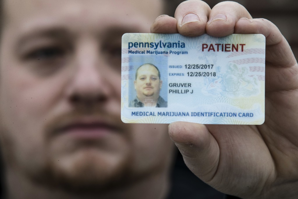 In this Wednesday, Jan. 10, 2018 photo Phil Gruver poses for a photograph with his Pennsylvania with his medical marijuana card in Emmaus, Pa. As gun-