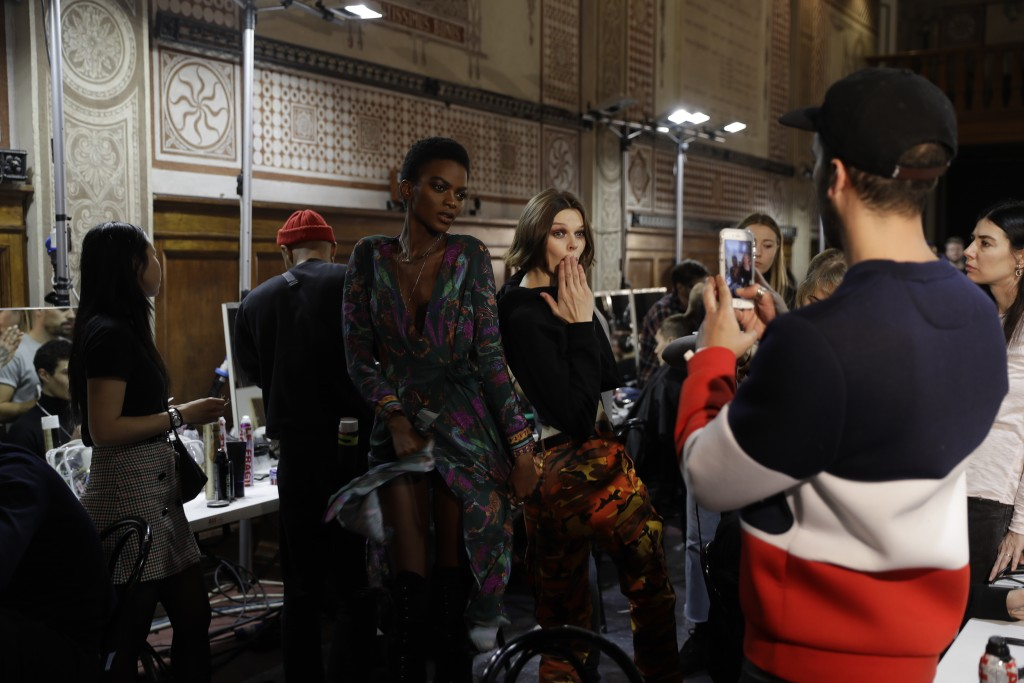Models wait backstage prior to the start of Versace men's Fall-Winter 2018-19 collection, that was presented in Milan, Italy, Saturday, Jan.13, 2018.