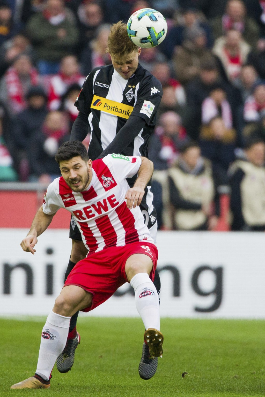 Cologne's  Milos Jojic, front, and Moenchengladbach's  Nico Elvedi  challenge for the ball during the German first division Bundesliga soccer match be