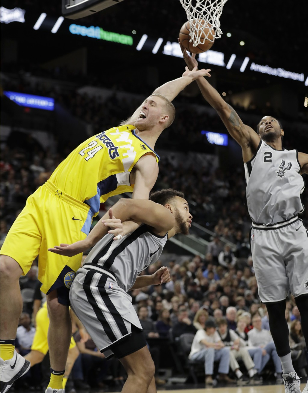 Denver Nuggets center Mason Plumlee (24) and San Antonio Spurs forwards Kyle Anderson (1) and Kawhi Leonard (2) vie for a rebound during the first hal