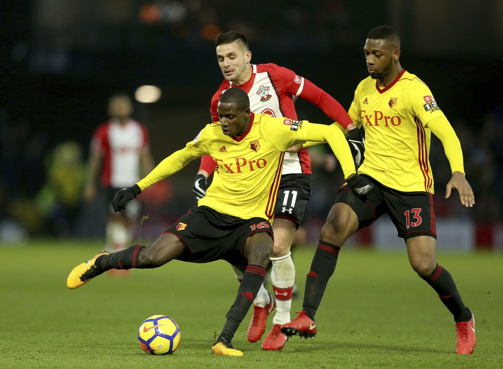 Watford's Abdoulaye Doucoure, left, and Southampton's Dusan Tadic, center, battle for the ball during the English Premier League soccer match at Vicar