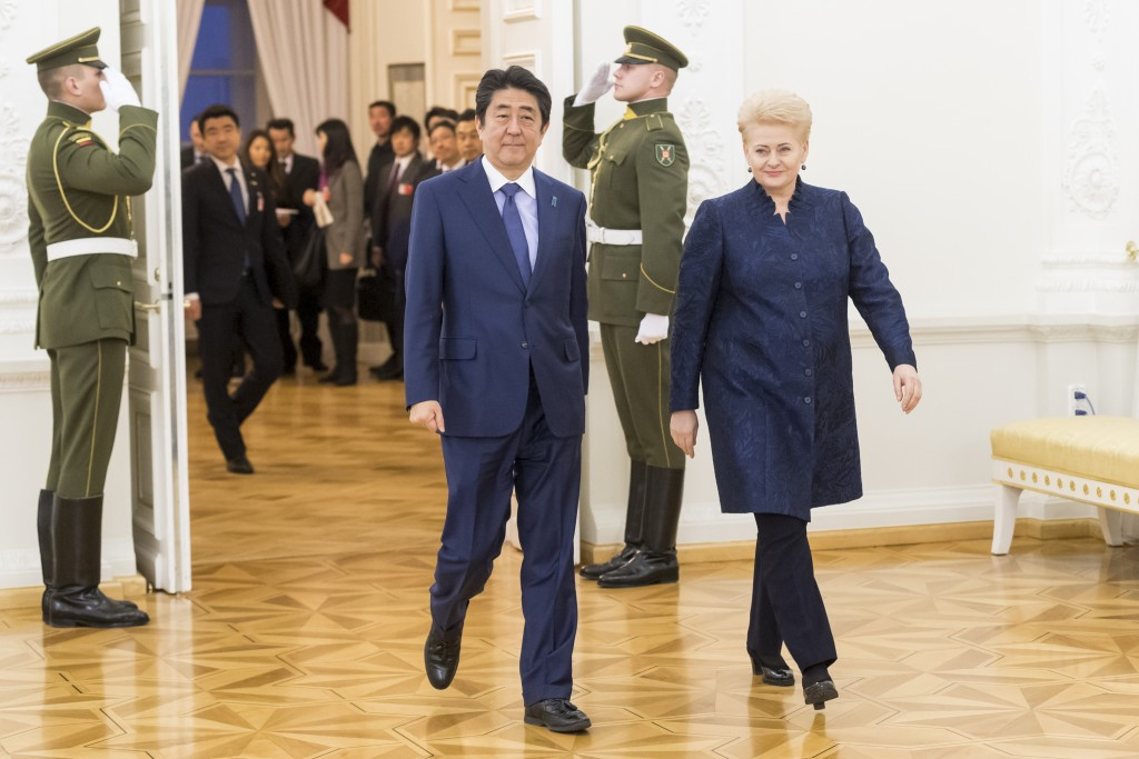 Lithuania's President Dalia Grybauskaite, right, and Japanese Prime Minister Shinzo Abe walk together for their meeting at the President's palace in V
