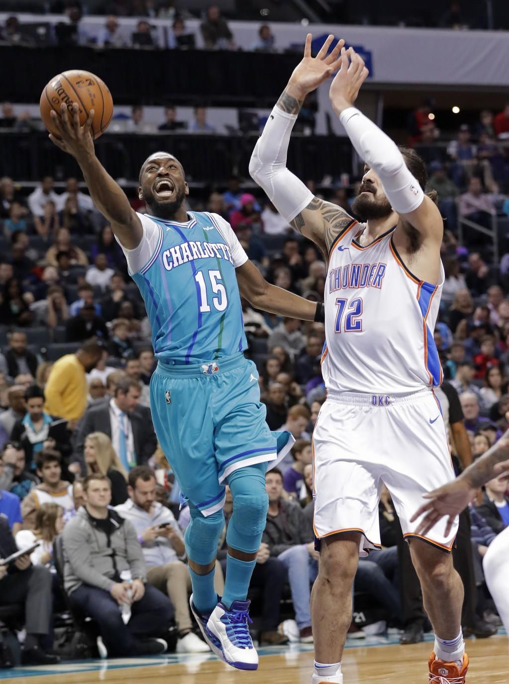 Charlotte Hornets' Kemba Walker (15) drives past Oklahoma City Thunder's Steven Adams (12) during the first half of an NBA basketball game in Charlott