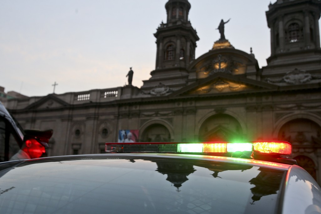 A police office stands guard outside the Cathedral in Santiago, Chile, Saturday, Jan. 18, 2018. President Michelle Bachelet is asking the country to r