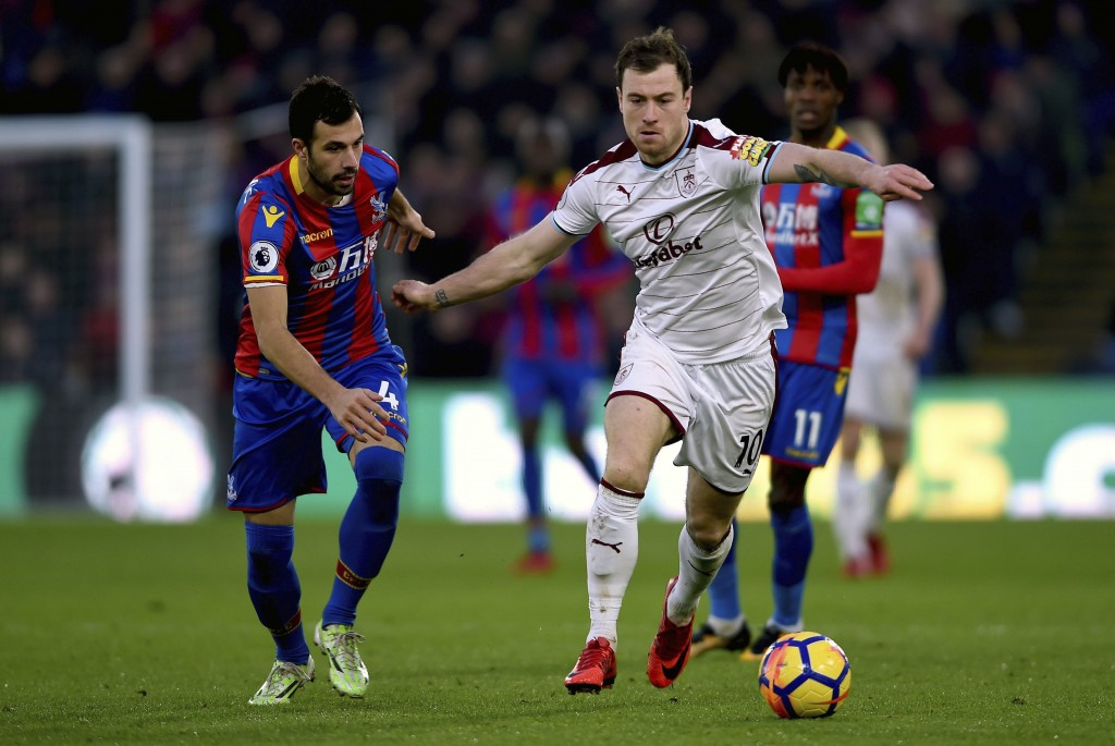 Crystal Palace's Luka Milivojevic, left, and Burnley's Ashley Barnes battle for the ball during the English Premier League soccer match at Selhurst Pa