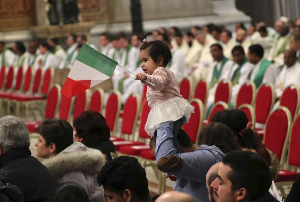 Stella, a ten-month toddler daughter of a Syrian refugee waves an Italian flag before a Mass on the occasion of the world day for migrants and refugee