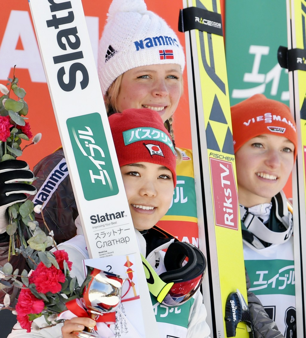 Maren Lundby of Norway, center, poses with second placed Japan's Sara Takanashi, left, and third placed Germany's Katharina Althaus, right, after Lund