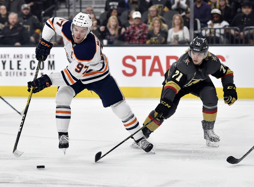 Edmonton Oilers center Connor McDavid (97) skates with the puck under pressure from Vegas Golden Knights center William Karlsson during the first peri
