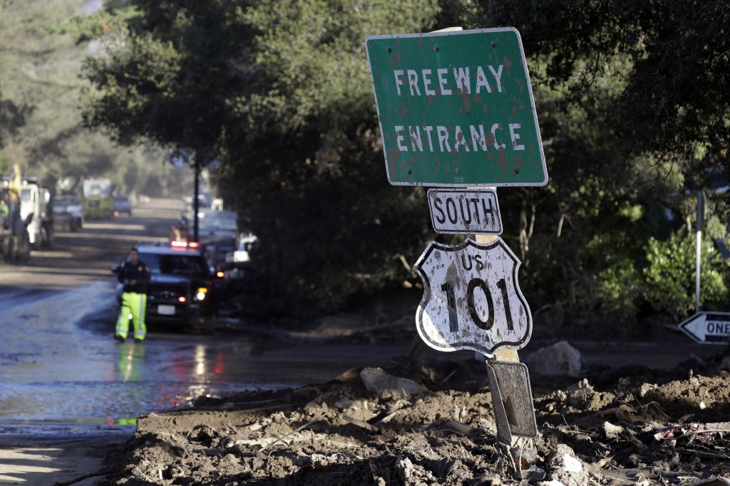 A mud-covered sign over the closed Highway 101 is seen at an overpass Saturday, Jan. 13, 2018, in Montecito, Calif.  Most of the people of Montecito,