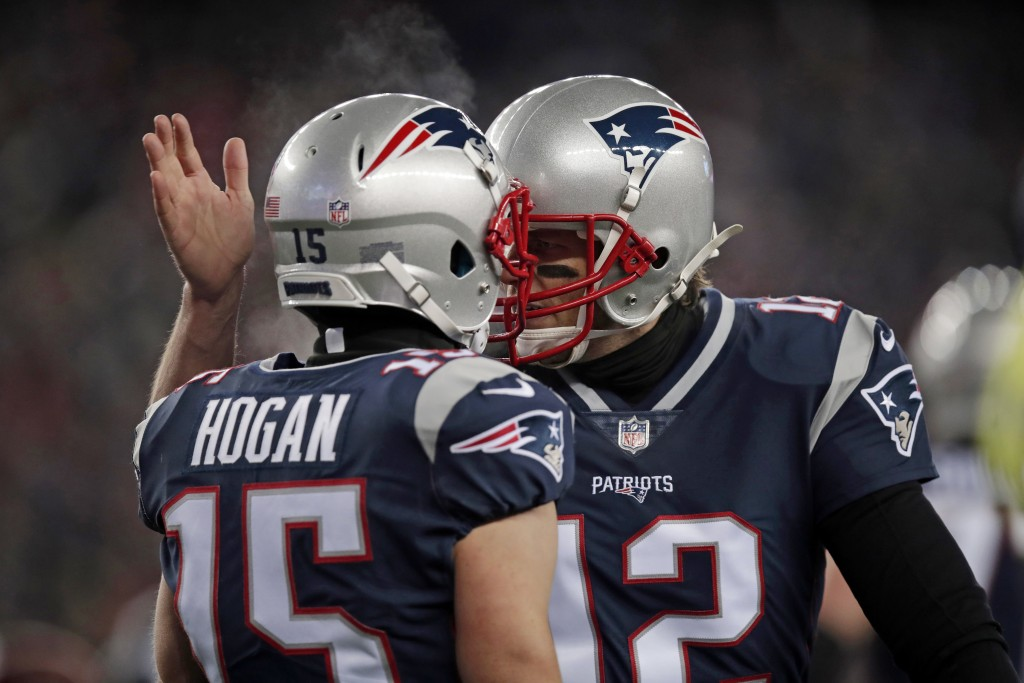 New England Patriots quarterback Tom Brady, right, celebrates his touchdown pass to Chris Hogan during the first half of an NFL divisional playoff foo
