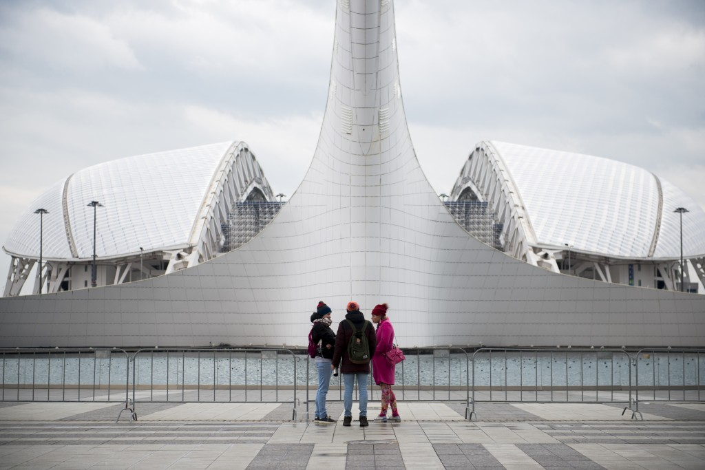 In this photo taken on Friday, Jan. 12, 2018, visitors talk in front of the Olympic flame cauldron and the Fisht Olympic Stadium in the Olympic Park i
