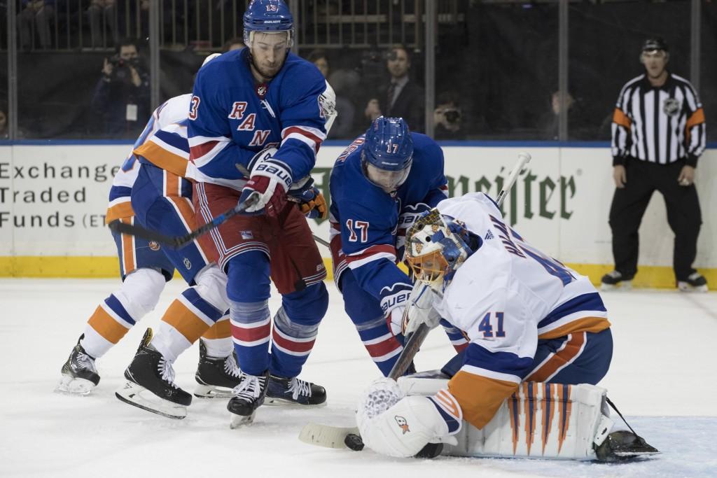 New York Islanders goaltender Jaroslav Halak (41) defends the net against New York Rangers right wing Jesper Fast (17) and center Kevin Hayes (13) dur