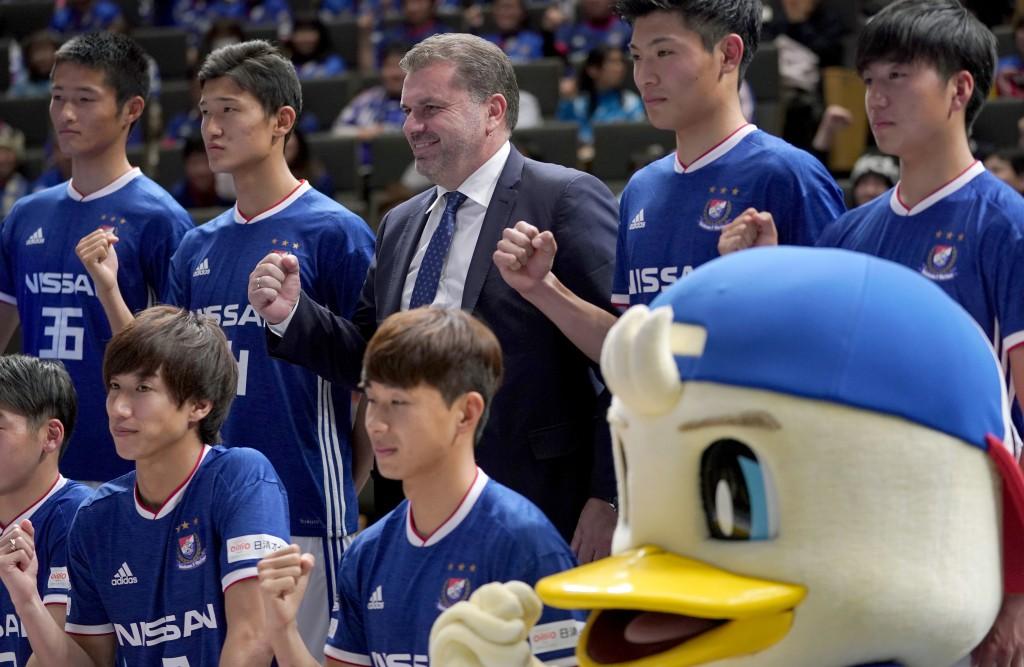 Yokohama F Marinos new head coach Ange Postecoglou of Australia poses with new players during a press conference in Yokohama, near Tokyo, Sunday, Jan.