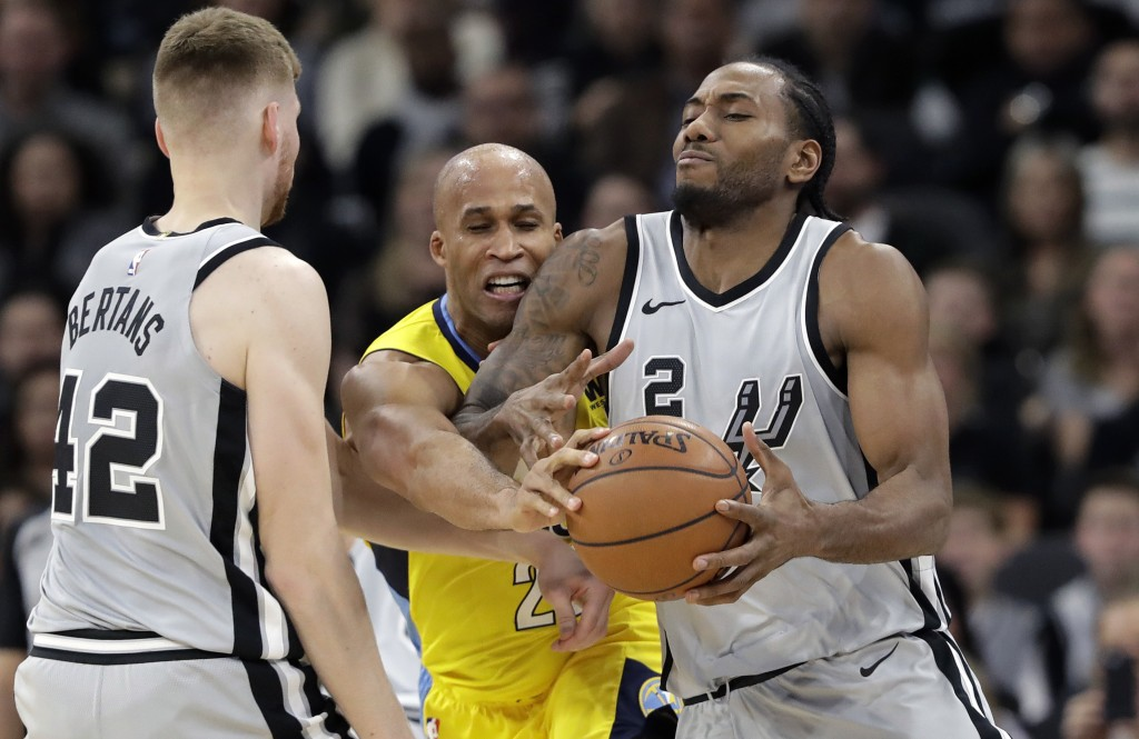 San Antonio Spurs forward Kawhi Leonard (2) is pressured by Denver Nuggets forward Richard Jefferson, center, during the first half of an NBA basketba