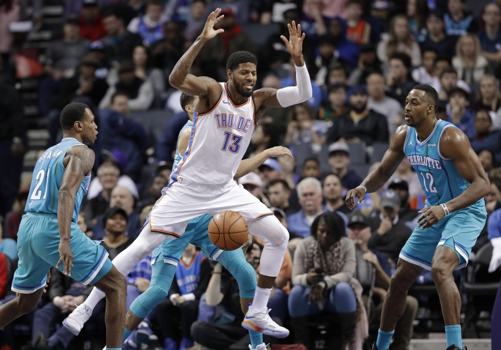 Oklahoma City Thunder's Paul George (13) loses the ball as he drives between Charlotte Hornets' Dwight Howard (12) and Treveon Graham (21) during the