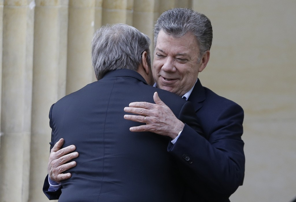 Colombia's President Juan Manuel Santos, right, embraces U.N. Secretary-General Antonio Guterres, during a welcoming ceremony at the presidential pala