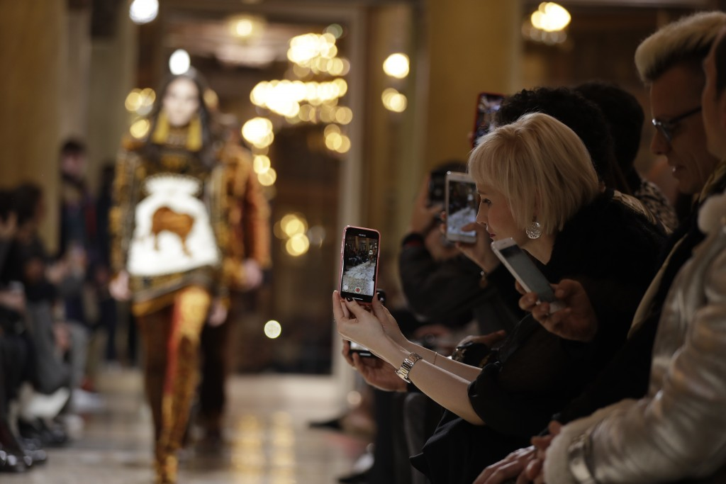 Spectators takes pictures of model wearing creations as part of Versace men's Fall-Winter 2018-19 collection, that was presented in Milan, Italy, Satu