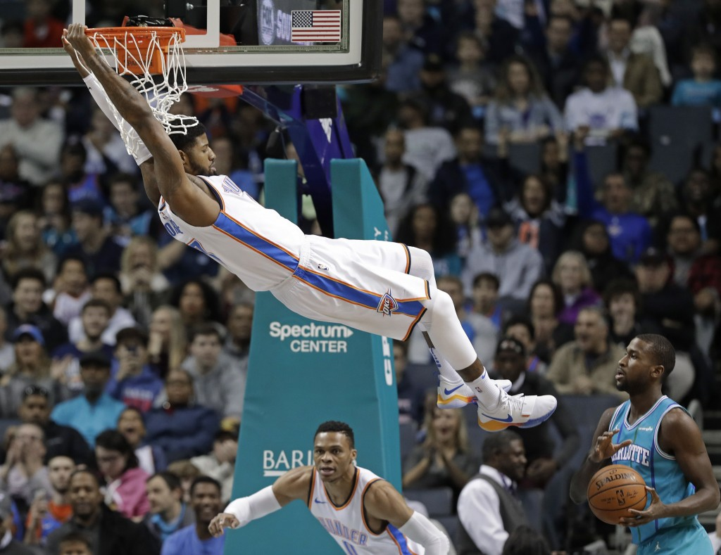 Oklahoma City Thunder's Paul George (13) hangs from the rim after a dunk against the Charlotte Hornets during the first half of an NBA basketball game