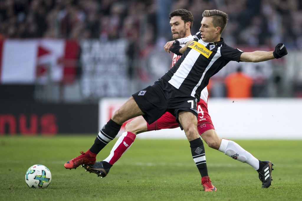 Cologne's s Jonas Hector left, and Moenchengladbach's Patrick Herrmann challenge for the ball during the German first division Bundesliga soccer match
