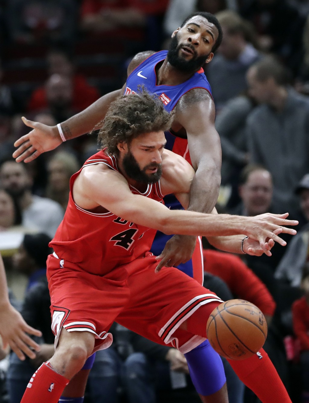 Detroit Pistons center Andre Drummond, top, and Chicago Bulls center Robin Lopez battle for the ball during the first half of an NBA basketball game S