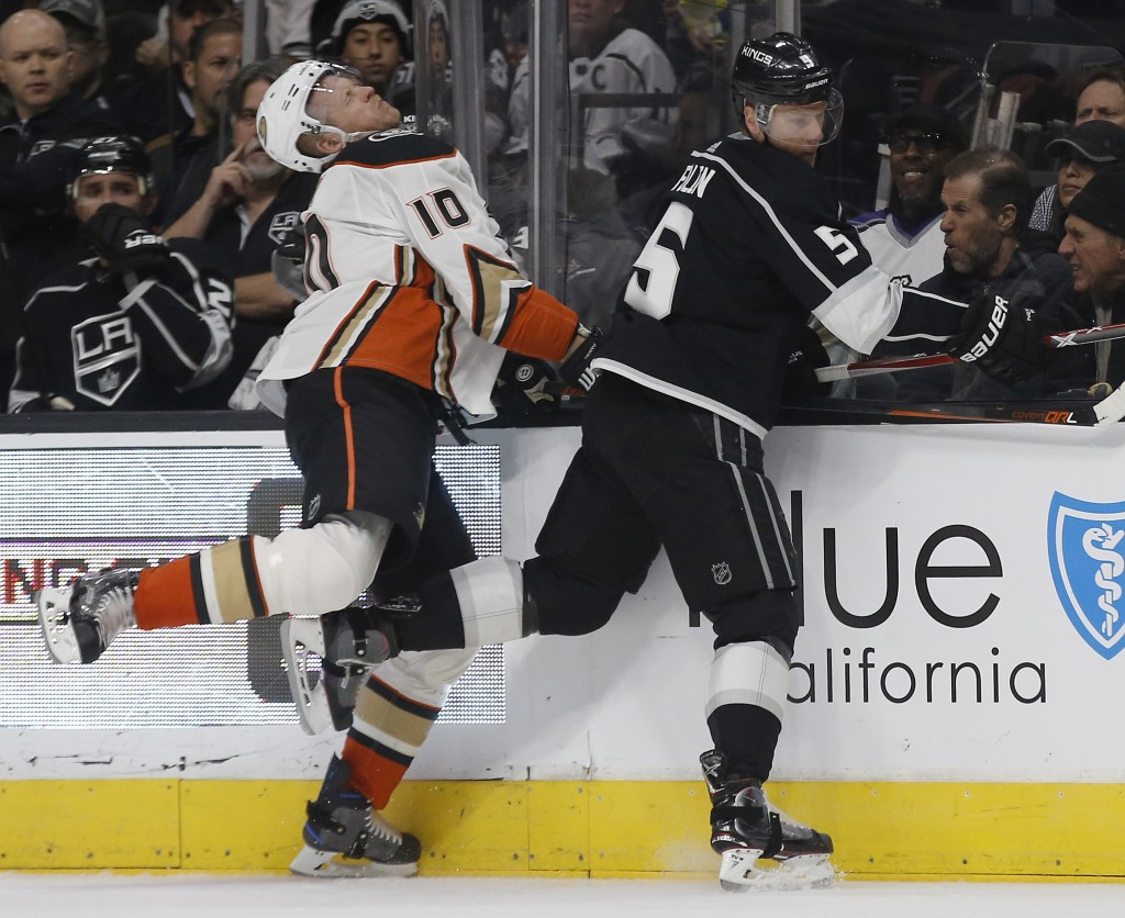 Los Angeles Kings defenseman Christian Folin, right, of Sweden, runs Anaheim Ducks right wing Corey Perry into the boards during the first period of a