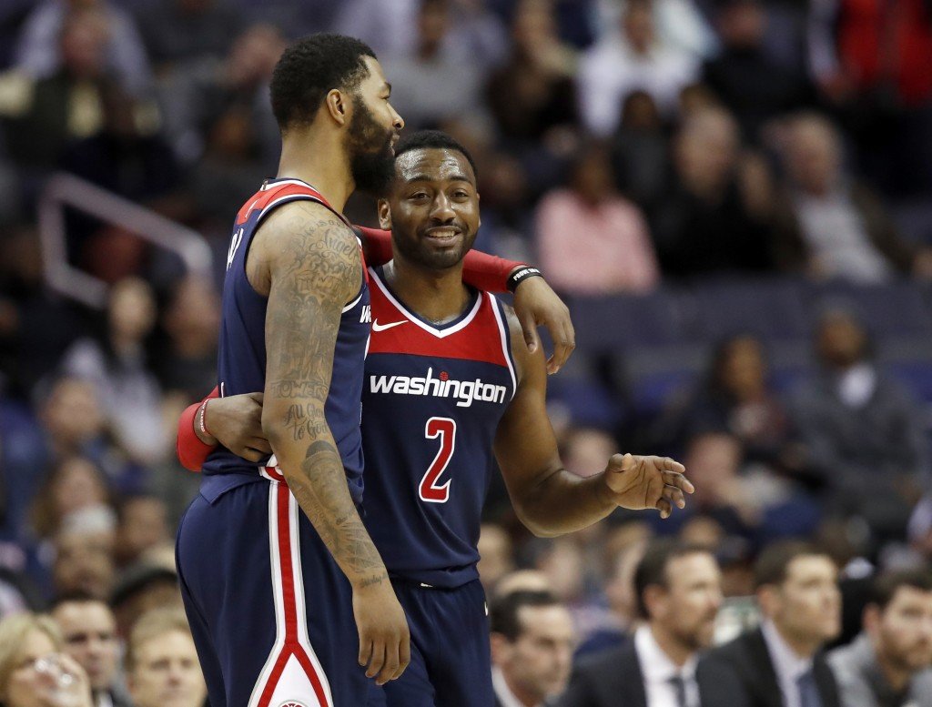 Washington Wizards forward Markieff Morris, left, and guard John Wall react after a play during the overtime portion of an NBA basketball game against