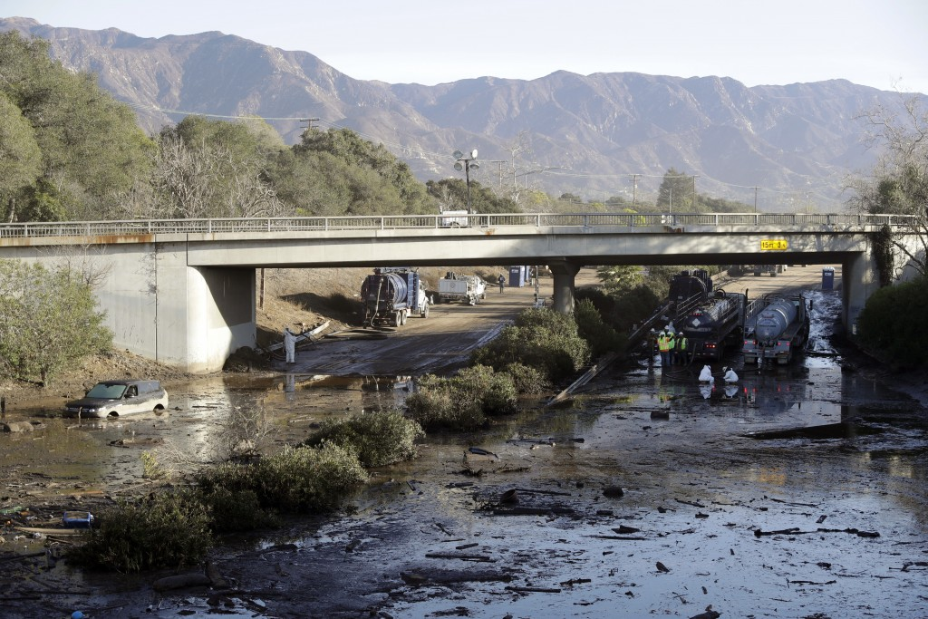 Crews work on clearing Highway 101 in the aftermath of a mudslide Saturday, Jan. 13, 2018, in Montecito, Calif. Most of the people of Montecito, a tow