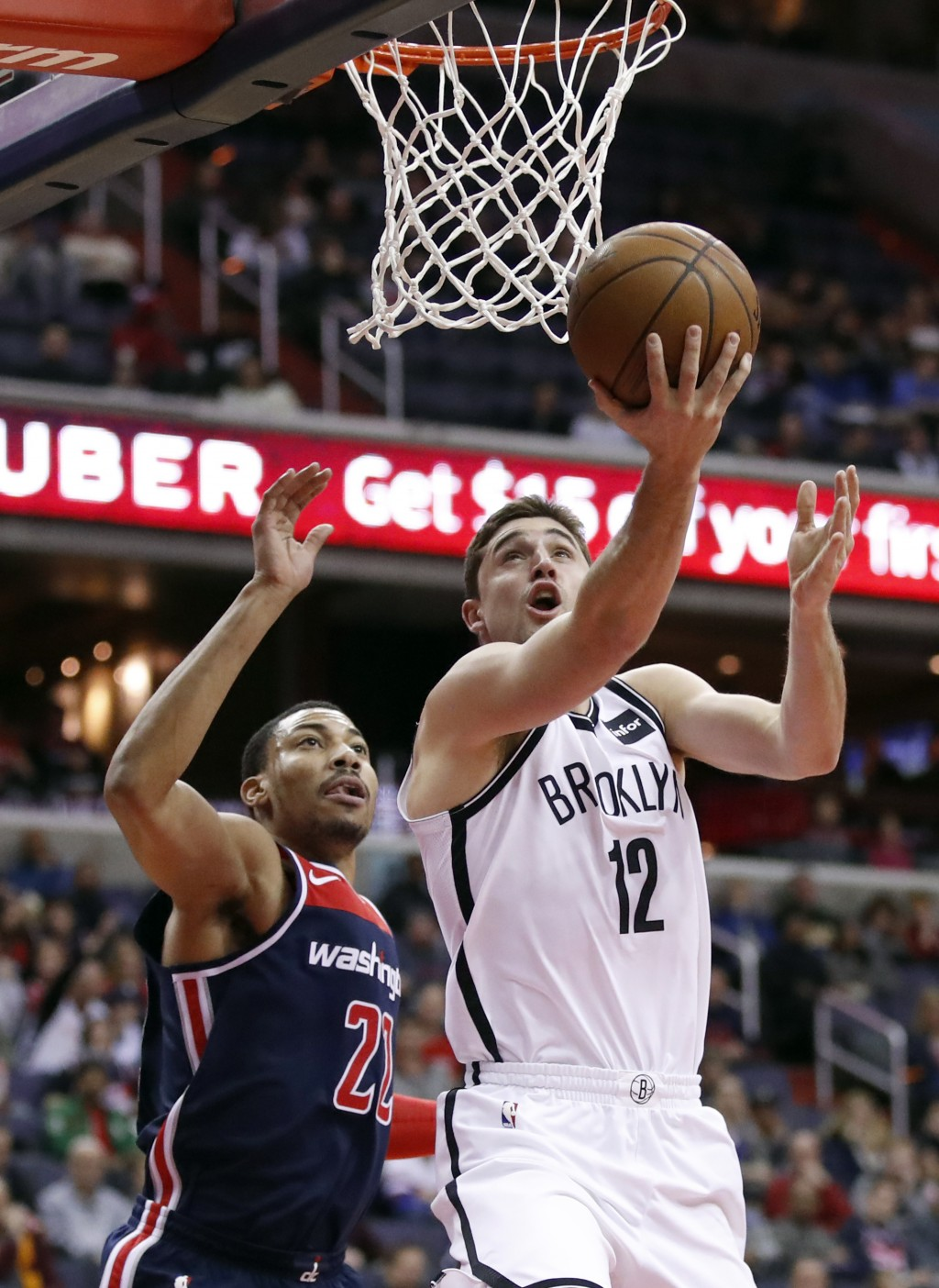 Brooklyn Nets guard Joe Harris (12) shoots past Washington Wizards forward Otto Porter Jr. (22) during the first half of an NBA basketball game Saturd