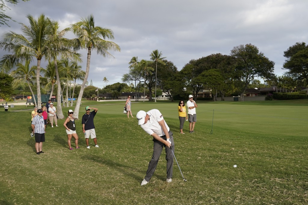 Tom Hoge, center, hits his ball out of the rough back into play on the 16th fairway during the third round of the Sony Open golf tournament, Saturday