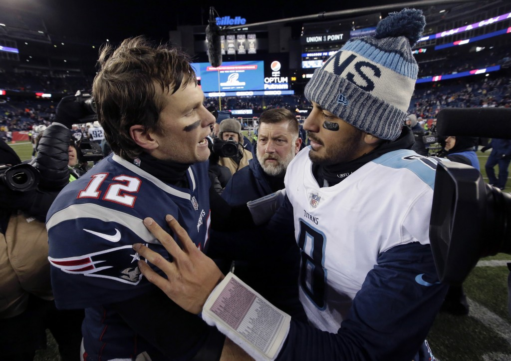 New England Patriots quarterback Tom Brady, left, and Tennessee Titans quarterback Marcus Mariota speak at midfield after an NFL divisional playoff fo