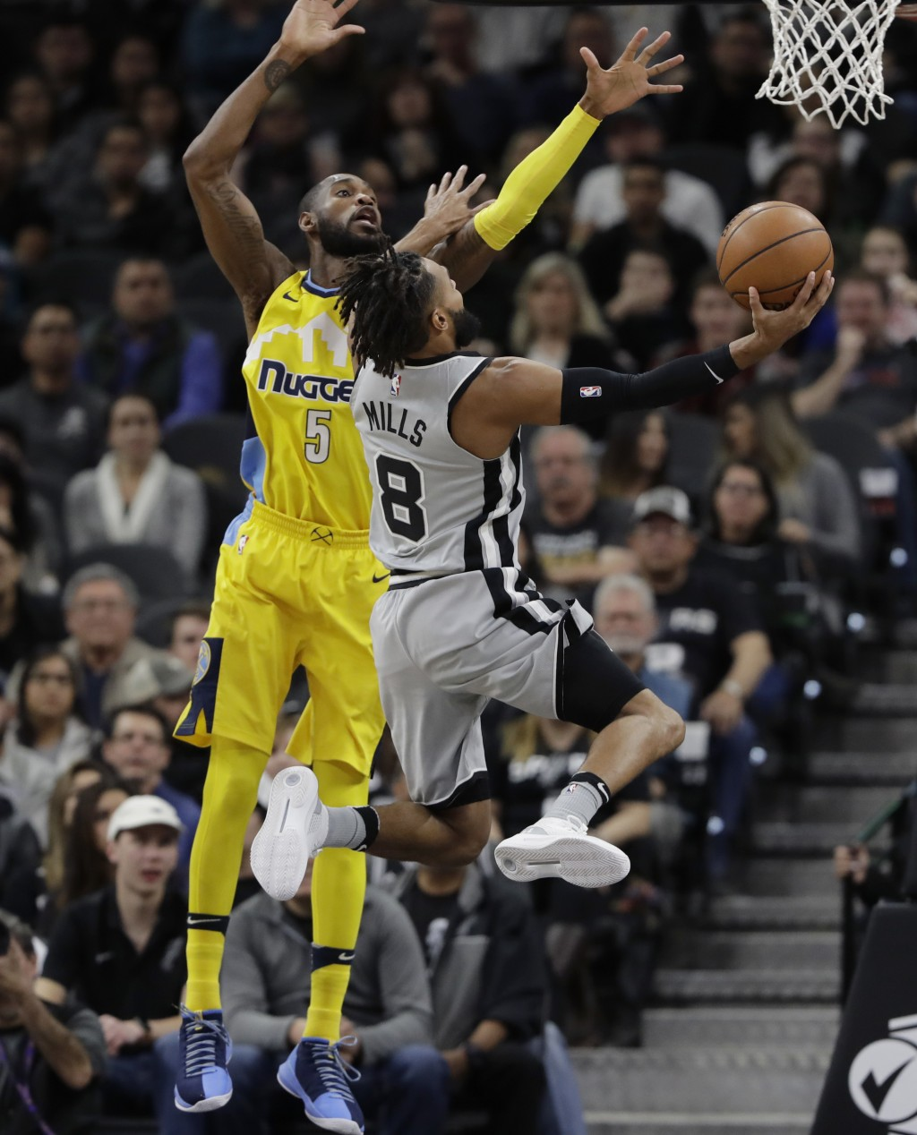 San Antonio Spurs guard Patty Mills (8) drives past Denver Nuggets guard Will Barton (5) during the first half of an NBA basketball game Saturday, Jan