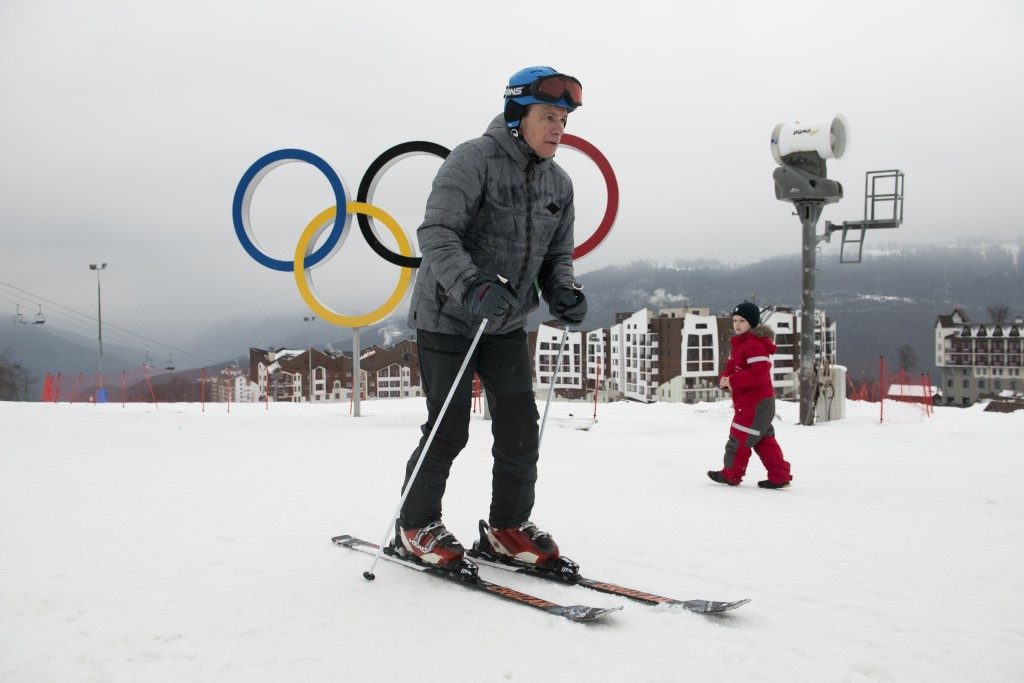 In this photo taken on Friday, Jan. 12, 2018, a visitor skis in front of the Olympic rings at the Rosa Khutor ski resort in Sochi, which hosted Olympi