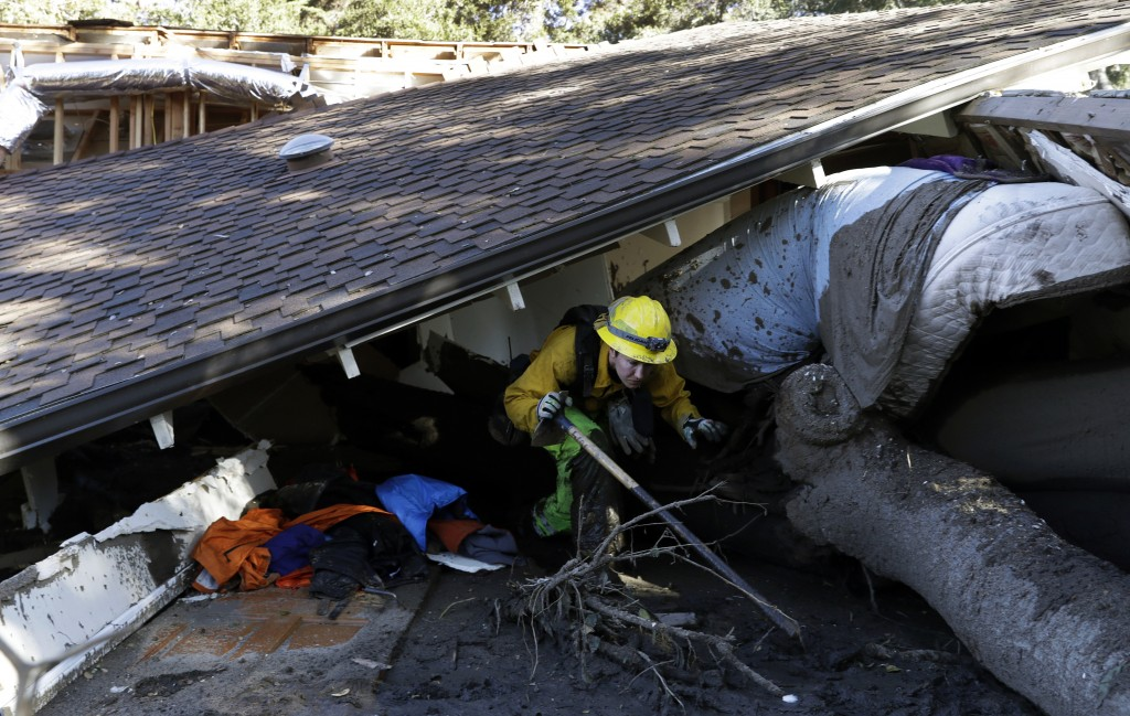 Colette Layton, bottom, of the Atascadero Fire Dept, searches a home Saturday, Jan. 13, 2018, in Montecito, Calif.  Most of the people of Montecito, a