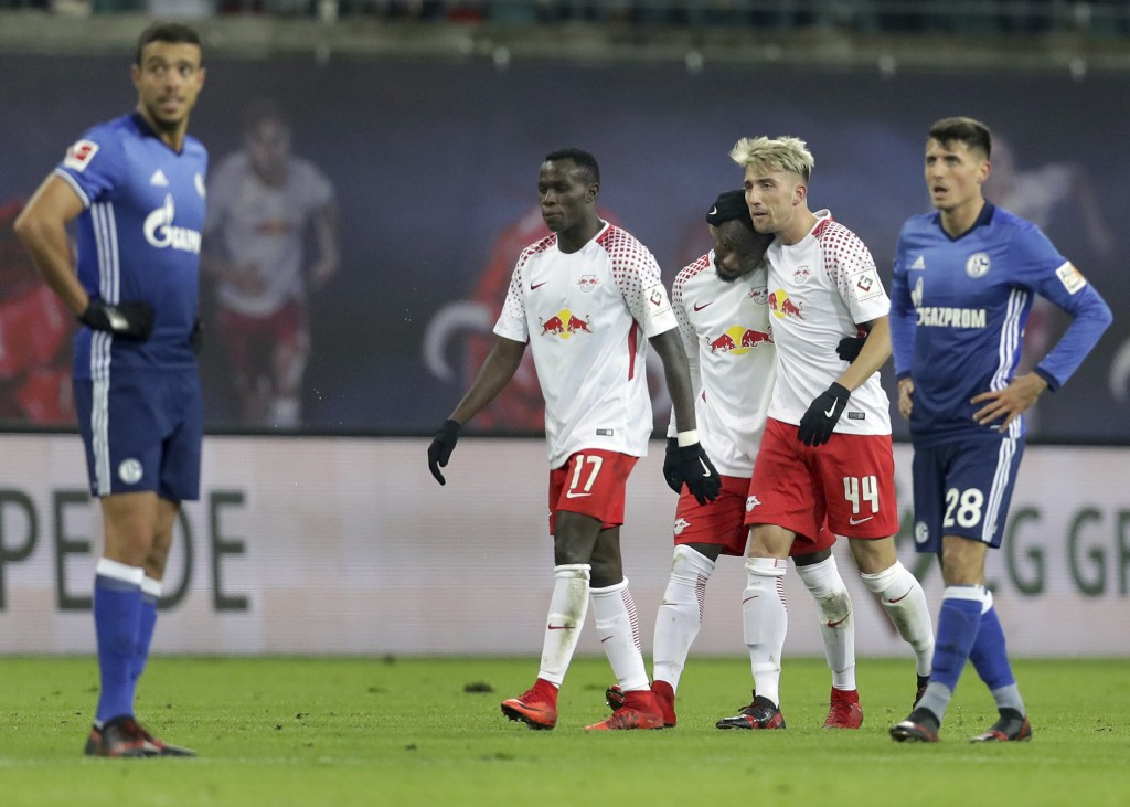 Leipzig's Kevin Kampl, 2nd right, hugs his teammate and scorer Naby Keita, center, as they celebrate the opening goal during the German Bundesliga soc