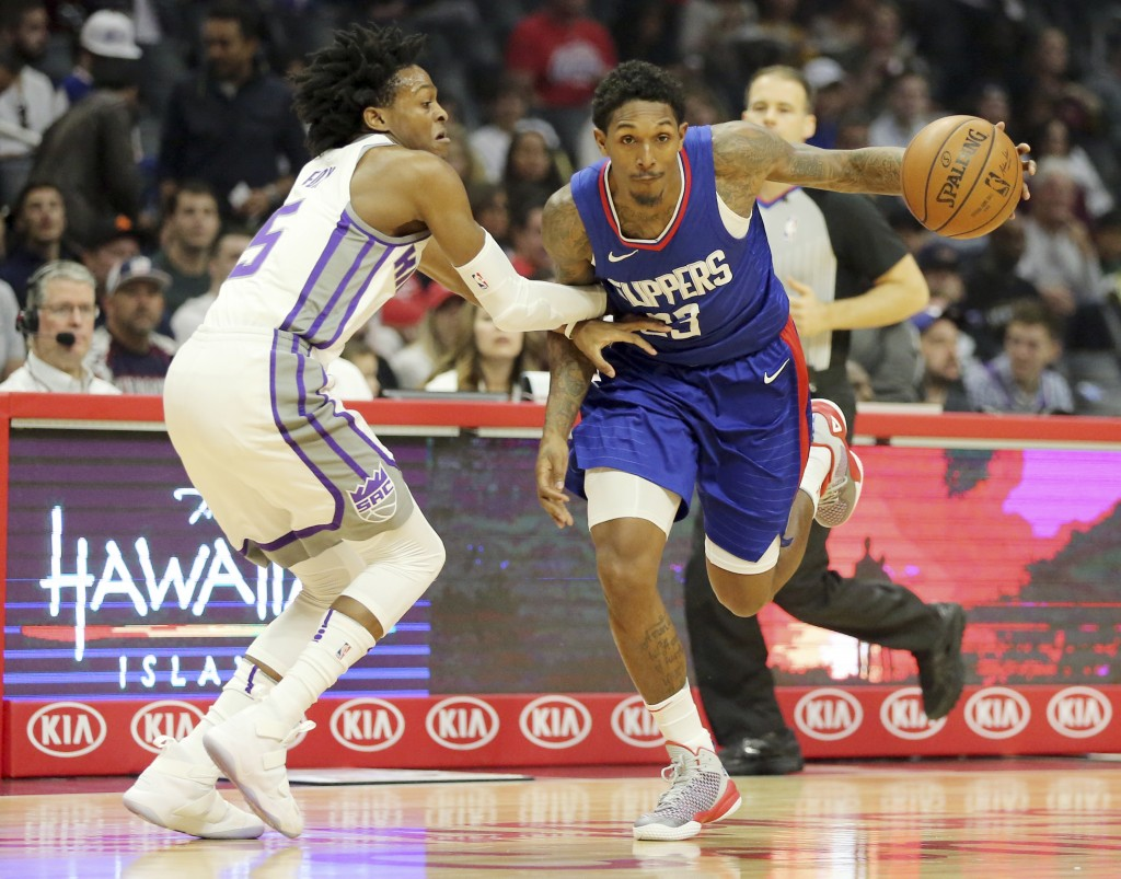 Sacramento Kings guard De'Aaron Fox (5) defends as Los Angeles Clippers guard Lou Williams (23) drives in the first period of an NBA basketball game i