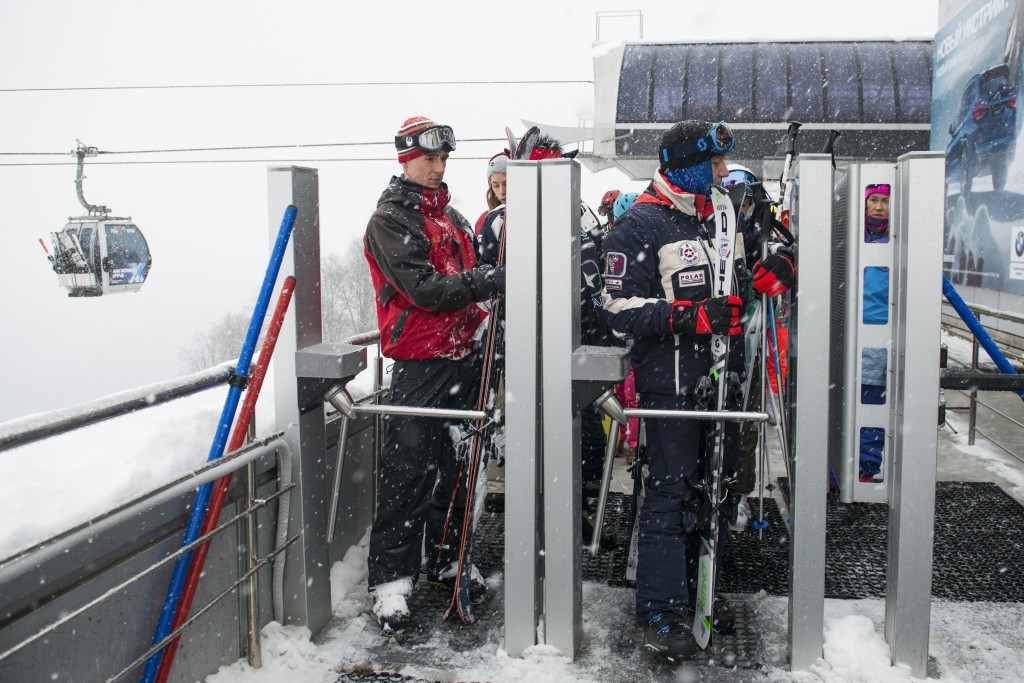 In this photo taken on Friday, Jan. 12, 2018, two visitors pass through the turnstile as they head to the piste at the Rosa Khutor ski resort in Sochi