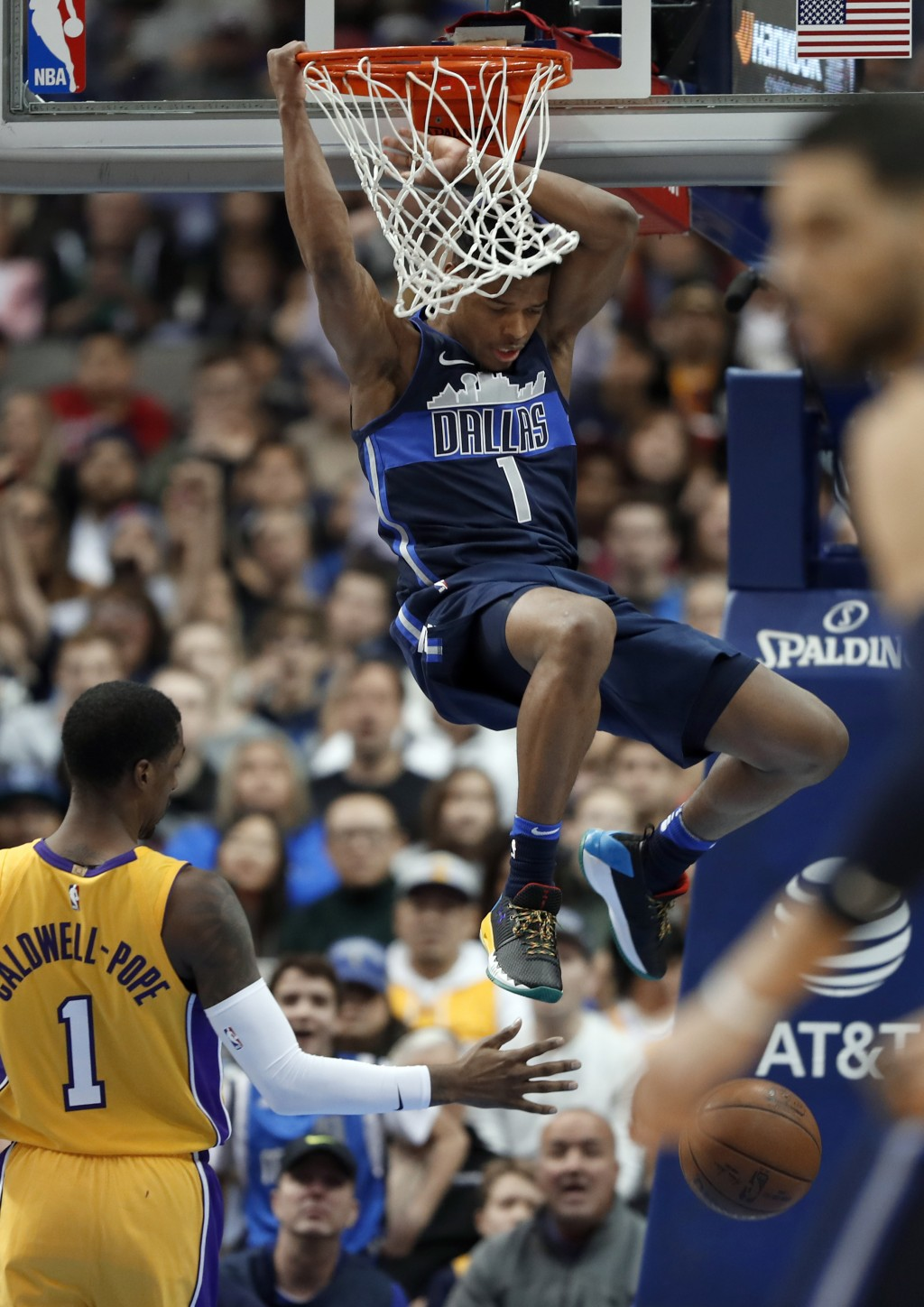 Los Angeles Lakers guard Kentavious Caldwell-Pope (1) watches as Dallas Mavericks guard Dennis Smith Jr., top, dunks in the first half of an NBA baske