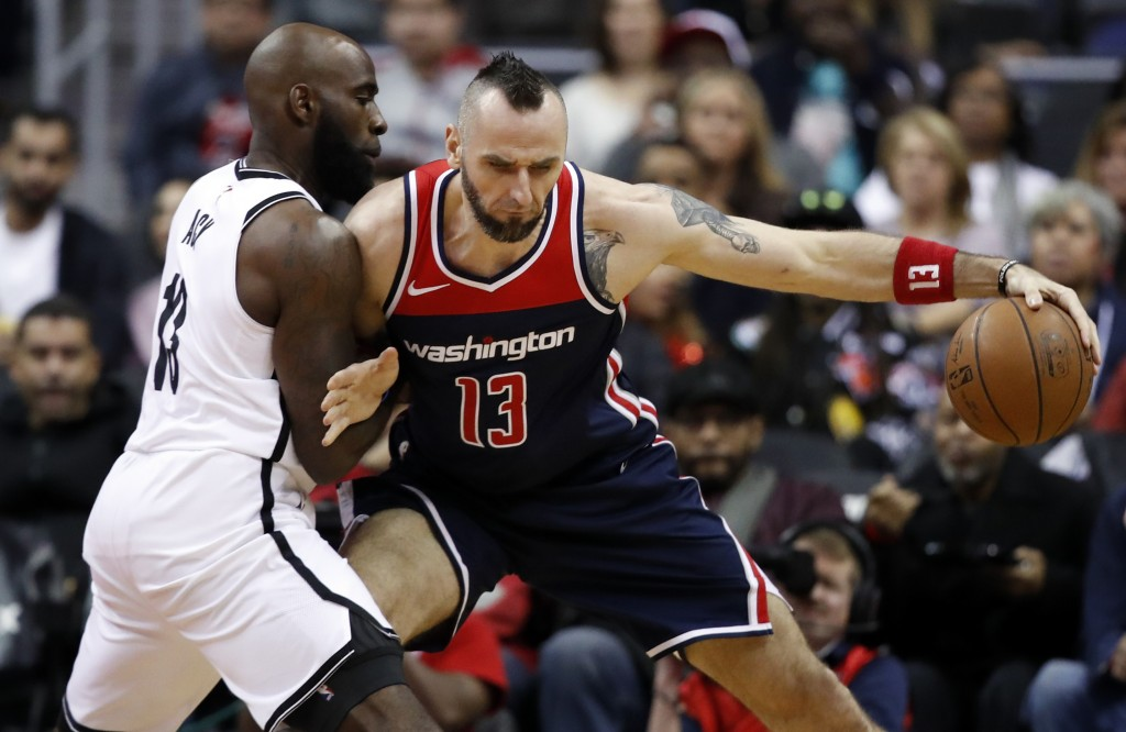 Brooklyn Nets forward Quincy Acy, left, defends against Washington Wizards center Marcin Gortat, right, from Poland, during the first half of an NBA b