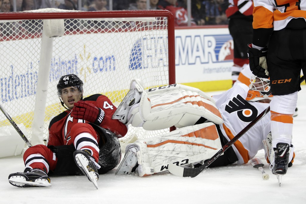 New Jersey Devils left wing Miles Wood, left, and Philadelphia Flyers goaltender Brian Elliott lie on the ice after colliding during the second period