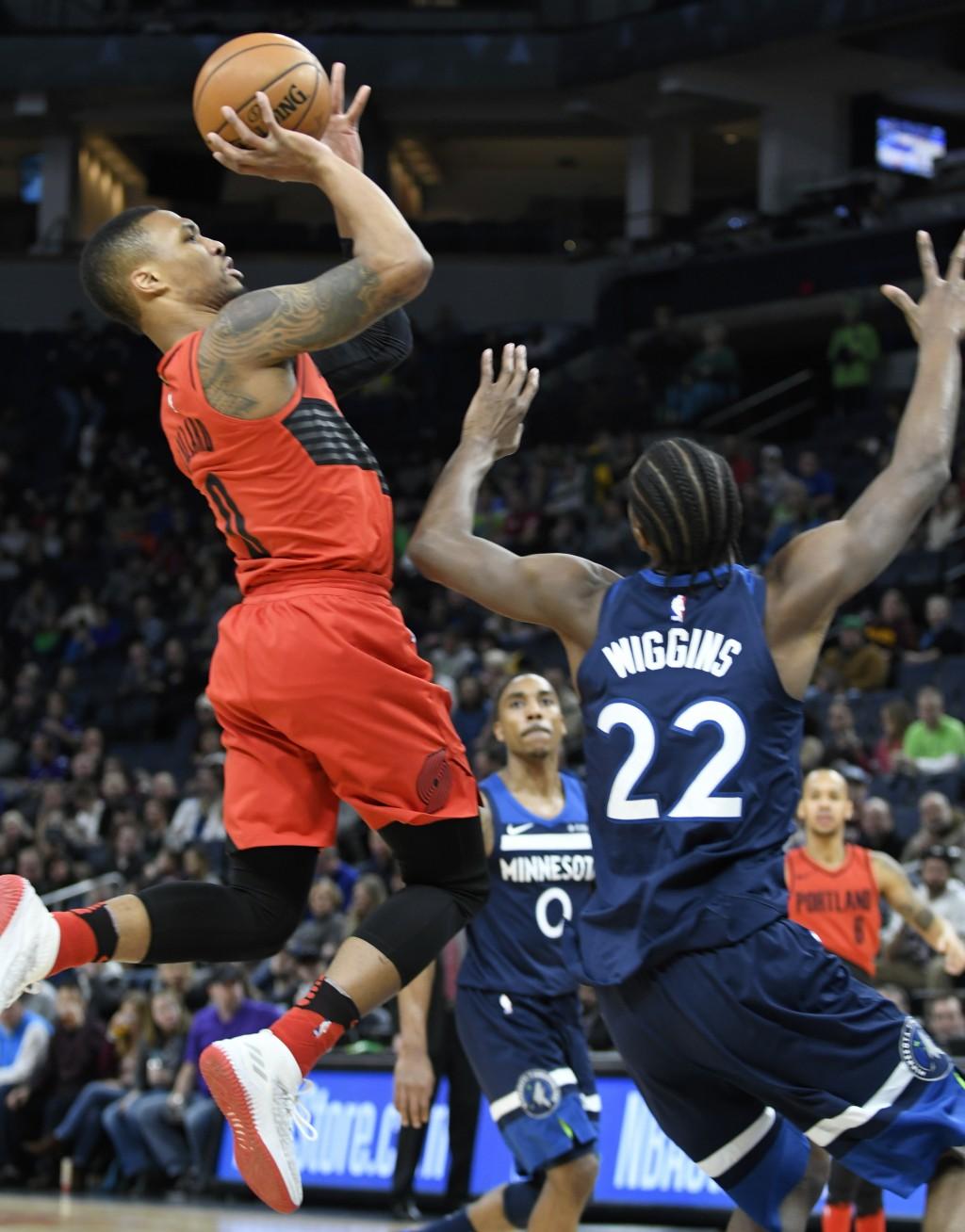 Portland Trail Blazers' Damian Lillard, left, shoots over Minnesota Timberwolves' Andrew Wiggins (22) in the first quarter of an NBA basketball game S...