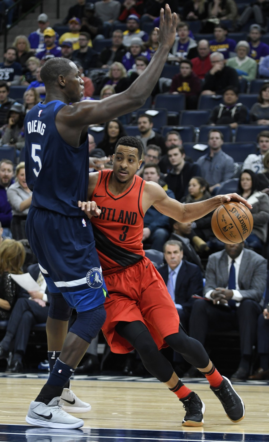 Portland Trail Blazers' C.J. McCollum, right, attempts to drive around the Minnesota Timberwolves' Gorgul Dieng, left, in the half of an NBA basketbal...