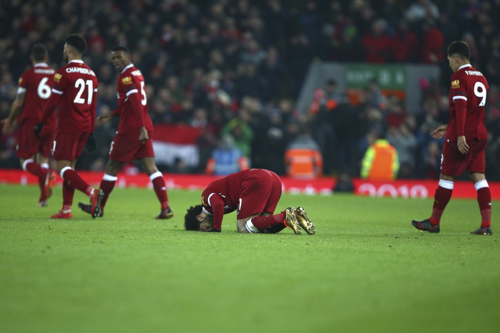 Liverpool's Mohamed Salah, center, celebrates scoring his side's fourth goal during the English Premier League soccer match between Liverpool and Manc