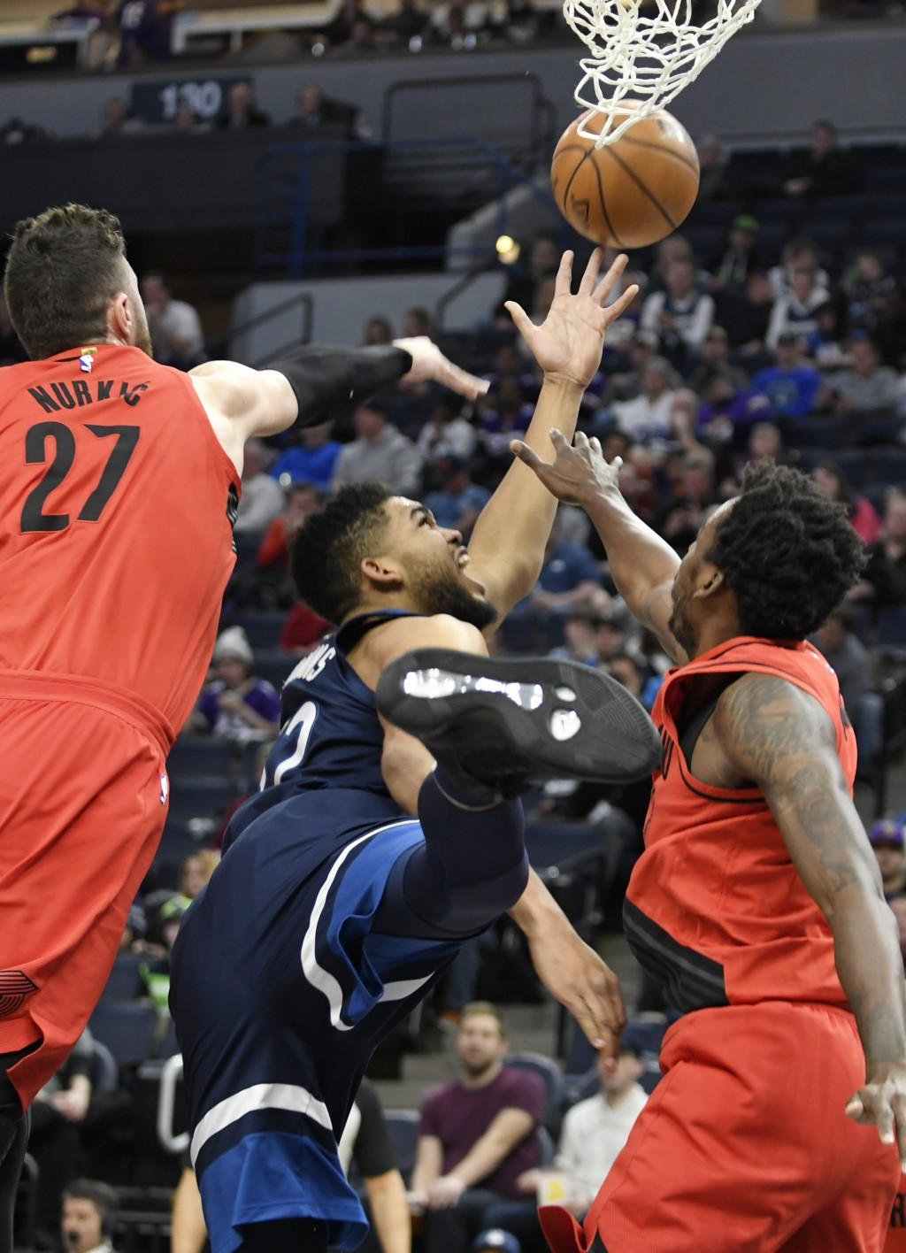 Minnesota Timberwolves' Karl-Anthony Towns, center, falls between Portland Trail Blazers' Jusuf Nurkic (27) and Al-Faroug Aminu, right,while getting o...