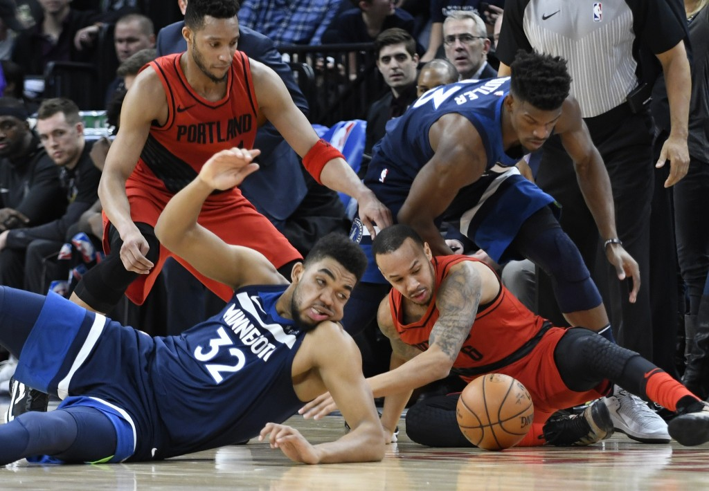 Minnesota Timberwolves' Karl-Anthony Towns, front left, and the Portland Trail Blazers' Damian Lillard, front right, go after the ball during the firs...