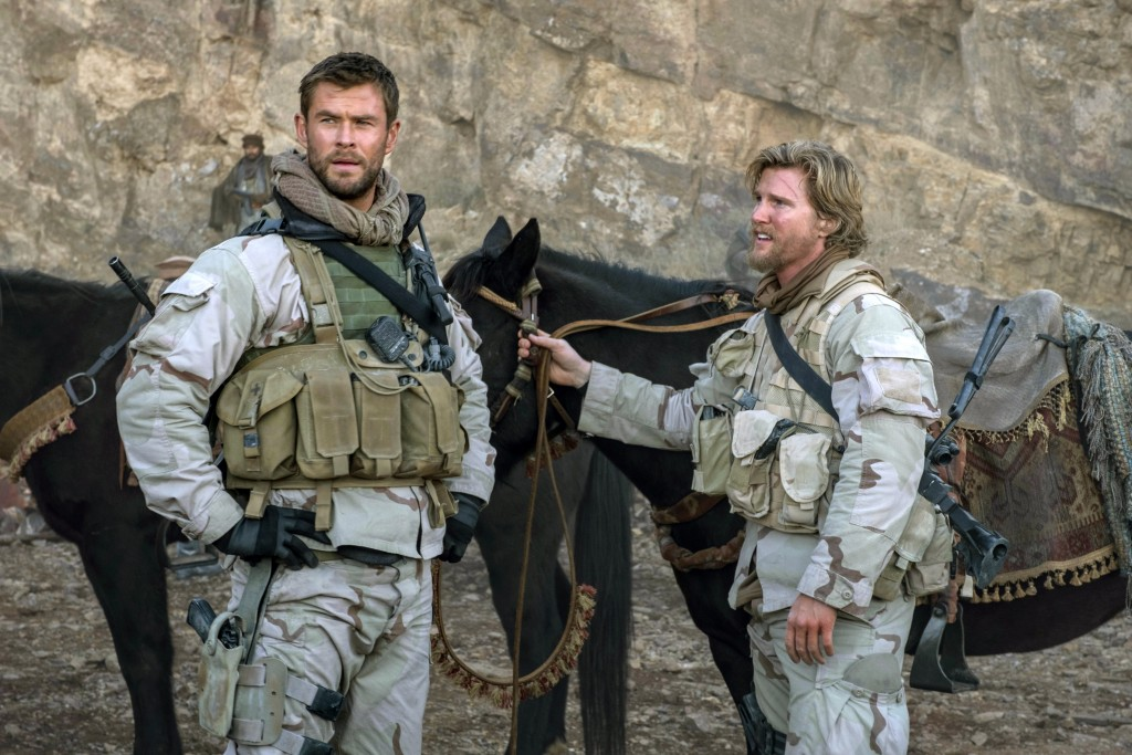 """This image released by Warner Bros. Entertainment shows Chris Hemsworth, left, and Thad Luckinbill in a scene from """"12 Strong."""" (David James/Warner Br..."""