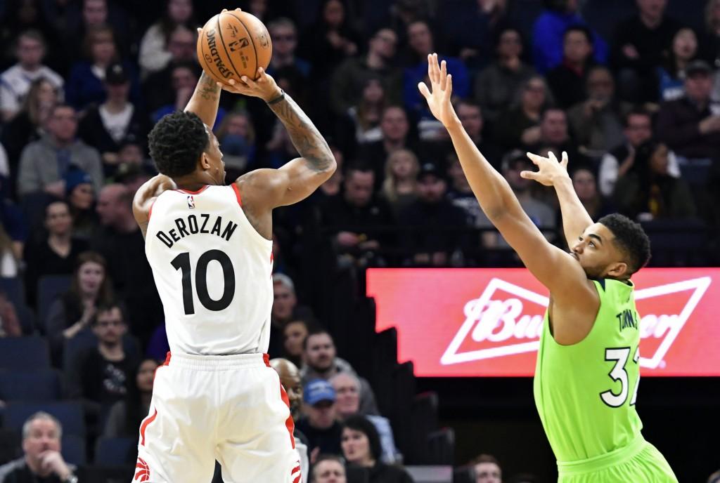 Toronto Raptors' DeMar DeRozan, left, shoots over Minnesota Timberwolves' Karl-Anthony Towns in the first half of an NBA basketball game Saturday, Jan...