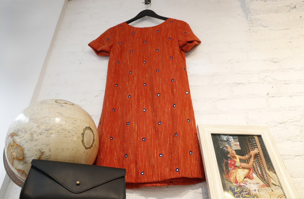 An orange Tikli shift dress with tiny mirrors embedded in the silk/cotton, handloom-blend fabric is displayed beside a photograph of an Indian woman w